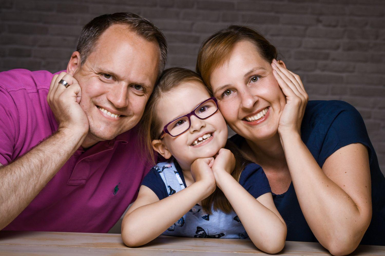 Glückliche Familie lächelt in die Kamera. Thema: CDG-Syndrom