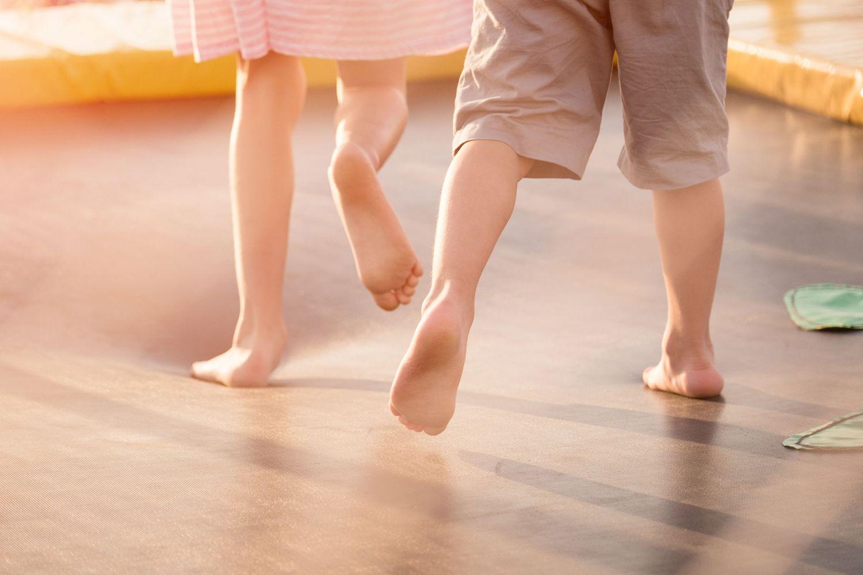 Kinderbeine mit nackten Füßen